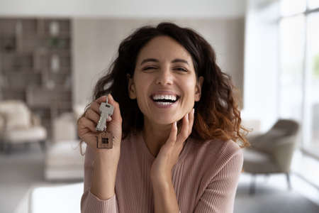 Headshot portrait of smiling Hispanic woman look at camera show keys to new home excited to move in. profile picture of happy Latino female renter buyer overjoyed to relocate. Renter, rent concept.