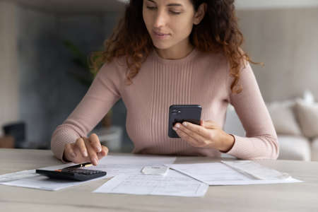 Young Hispanic woman sit at desk calculate household expenses expenditures on machine pay online on cellphone. Latin female renter manage family budget finances using smartphone. Banking concept.