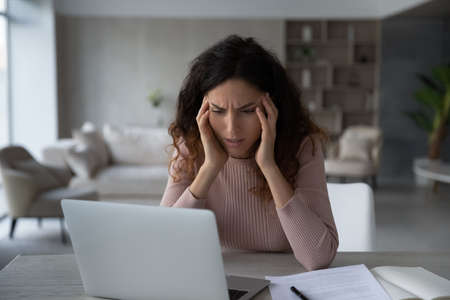 Unhappy Latin woman work on computer feel stressed with job or deadline. Upset distressed Hispanic female look at laptop screen study on gadget lack inspiration or suffer from migraine or headache. Banque d'images