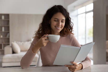 Happy millennial Latino woman sit at table at home read interesting book drink coffee or tea relaxing. Smiling young Hispanic female rest on weekend in cozy living room enjoy novel with cup or mug.