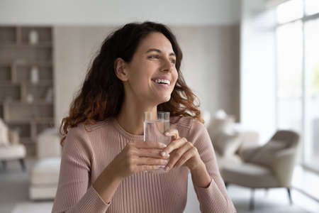 Smiling young Hispanic woman hold glass enjoy clean mineral water look in distance dreaming visualizing. Happy millennial Latino female feel dehydrated drink aqua. Healthy lifestyle, habit concept. Banque d'images
