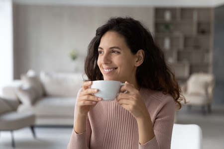 Happy millennial Latino woman drink coffee or tea from mug cup look in distance dreaming thinking of opportunities achievements. Smiling Hispanic female enjoy leisure free time at home visualizing.