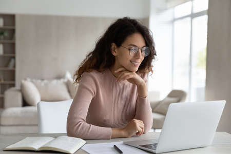 Happy Hispanic woman in glasses sit at desk work online on laptop make notes handwrite. Smiling Latino female student study on web on computer, take distant course or training on gadget at home. Banque d'images