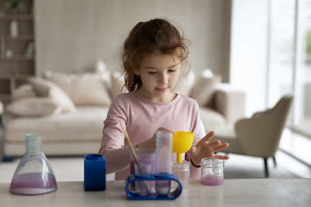 Little teen ethnic girl child make experiments with chemistry children laboratory game at home. Small biracial kid have fun play with lab, engaged in playful scientific activity. Hobby concept. Banque d'images