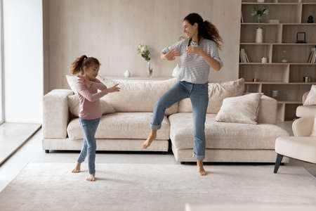 Overjoyed young Latino mother and little biracial daughter dance together in cozy living room. Smiling Hispanic mom and small teen ethnic girl child have fun celebrate relocation to new home. Banque d'images