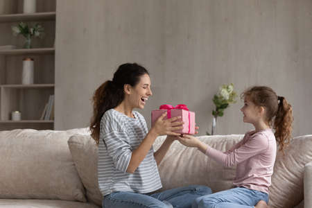 Loving small biracial daughter congratulate greet excited young Hispanic mom with birthday anniversary. Happy little ethnic girl child give gift box make surprise present for smiling Latin mom. Banque d'images
