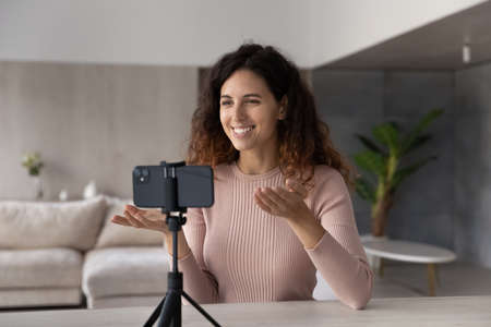 Happy young Latino woman look at cellphone screen have webcam virtual digital event lesson on device at home. Smiling Hispanic female talk speak on video call online on smartphone. Blogging concept. Banque d'images