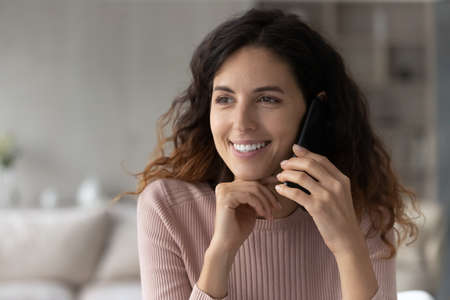Smiling young Hispanic woman hold modern smartphone gadget talk speak on electronic device. Happy Latino female have cellphone call use good mobile provider connection. Technology concept.
