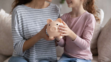 Crop close up of smiling Hispanic mom and biracial daughter hold piggy bank recommend family savings. Happy Latin ethnic mother and teen girl child use piggybank care of budget for money investment.