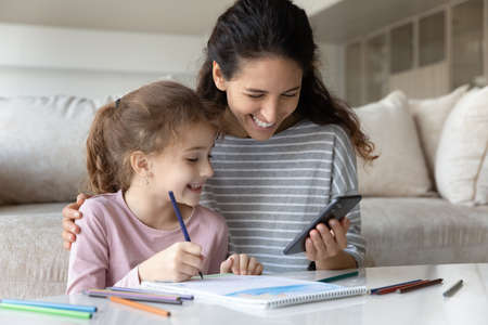 Smiling Hispanic mother and small biracial daughter have fun drawing using modern smartphone gadget. Happy Latino mom and ethnic girl child enjoy painting have online video lesson on cellphone.