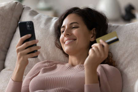 Happy young Hispanic female buyer client shopping online on cellphone with credit debit card. Smiling millennial Latin woman make payment buy on internet using smartphone. Consumerism concept.