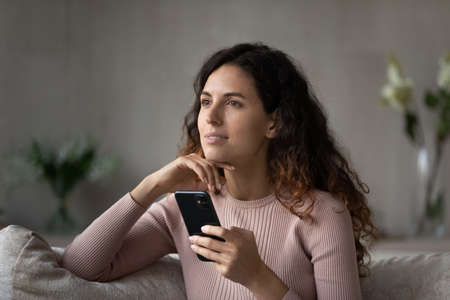 Pensive millennial Latino woman rest on couch at home use modern smartphone gadget look in distance dreaming visualizing. Thoughtful young Hispanic female relax at home browsing cellphone device.
