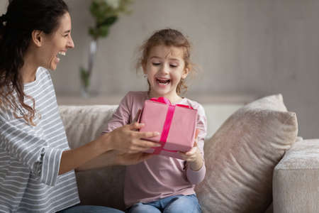 Smiling young Latin mom give wrapped gift box to excited small biracial daughter congratulate with birthday. Happy loving Hispanic mother make surprise present to overjoyed ethnic girl child at home.