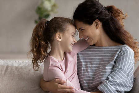 Happy young Hispanic mother and small teen ethnic daughter touch foreheads enjoy tender close family moment together. Smiling Latin mom and little biracial girl child hug show love and care.