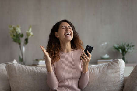 Overjoyed millennial Hispanic woman feel euphoric win online lottery on cellphone gadget. Smiling young Latino female relax at home triumph read good news get promotion notice on smartphone.