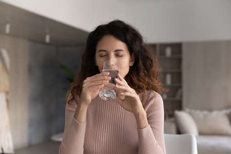 Thirsty millennial Latino woman feel dehydrated drink clean clear mineral still water from glass. Young Hispanic female enjoy pure aqua for body refreshment. Healthy lifestyle, hydration concept. Banque d'images