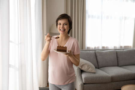 Portrait of smiling pregnant woman eating chocolate cake at home, happy young future mom enjoying pastry, sugar free dessert during pregnancy, holding plate with piece of pie, guilty pleasure