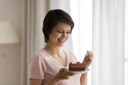 Close up smiling beautiful woman eating chocolate cake, enjoying pastry dessert, young female holding plate with piece of pie, feeling excited and happy, celebrating birthday, guilty pleasure Banque d'images