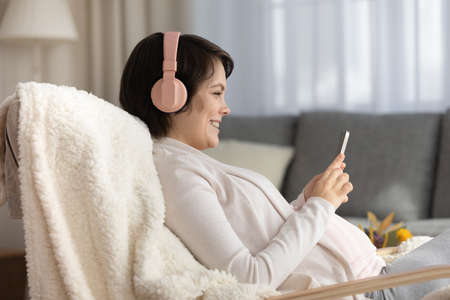Side view smiling pregnant woman in headphones using smartphone, looking at screen, enjoying leisure time, happy young future mom listening to music or watching video in social network, having fun