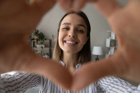Close up smiling beautiful young woman showing heart symbol with fingers to camera, demonstrating affectionate loving feelings. Happy sincere millennial female client giving positive feedback.