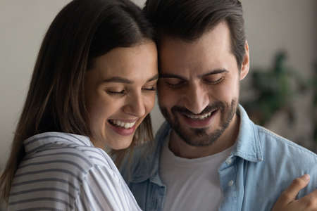 Head shot loving happy young married caucasian couple cuddling, showing tender affectionate feelings indoors. Dreamy emotional millennial man and woman enjoying peaceful moment together at home. Banque d'images