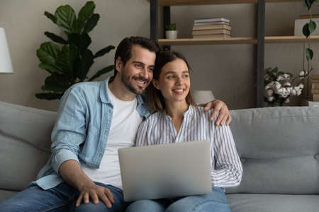Happy bonding young family couple sitting on couch with computer on laps, looking in distance, dreaming of good future, planning weekend or vacation together, thinking on received email with good news
