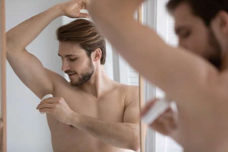 Calm handsome young well built man using deodorant, applying antiperspirant on underarm armpit skin after shower in bathroom at mirror, caring for hygiene, preventing sweating. Bath routine concept