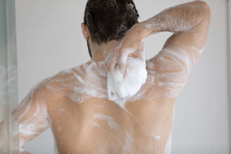 Back of handsome athletic wet young man taking shower, rubbing muscular body with foamy sponge, soap, cleansing gel. Male morning bath routine, daily hygiene, bodycare concept. Rear view