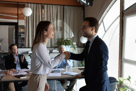 Happy boss expressing recognition, acknowledge to excited proud best employee, congratulating on career promotion, appreciating good job, giving positive feedback and handshake on corporate meeting