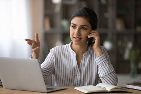 Young confident Indian businesswoman sit at desk at home office work online on laptop talk speak on smartphone. Mixed race female busy using computer have distant cellphone call with client.