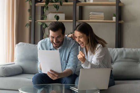 Young 30s couple feels euphoric look very happy scream with joy read good unbelievable news in paper letter document. Overjoyed spouses get pleasant message celebrate opportunity receive offer concept Imagens