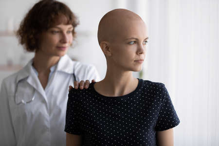 Young female oncologist putting hands on shoulder of stressed bald ill woman, giving psychological support to patient during chemotherapy, dreaming of effective treatment looking in distance.