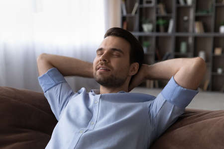 Sweet home. Peaceful young casual guy relax alone on comfy couch hands over head enjoy breathing cool fresh air dream nap meditate. Satisfied millennial male chill indoors on weekend breath deep rest