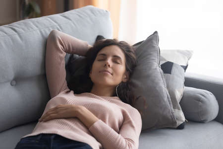 Peaceful woman closed her eyes take break lying sleeping on comfy couch having day nap resting alone in living room, breath fresh conditioned air, reduce fatigue, relish day off at modern home concept Imagens