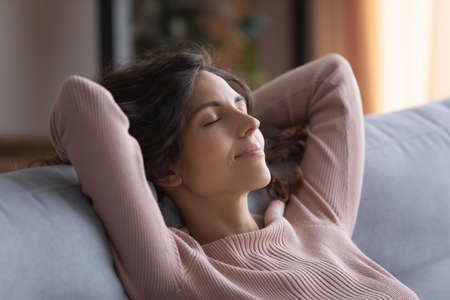 Smiling serene Hispanic woman close her eyes put hands behind head breath fresh conditioned air inside of modern living room, enjoy stress-free day off alone at home. Daydreams, peace of mind concept Banque d'images