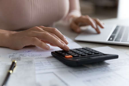 Close up young woman using calculator, summarizing utility bills, managing household budget, planning domestic savings or investments, financial accounting using e-banking application concept. Stock fotó
