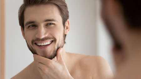 Close up view handsome male face reflecting in mirror, touch bristled chin in front of mirror feels satisfied after facial shaving, cream good results. Morning routine, self-hygiene, skincare concept Stock Photo