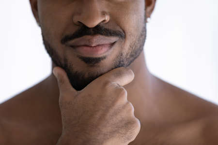 Close up cropped front face view handsome sensual 35s African ethnicity guy with shoulders, hand touches bearded chin. Self-groom, skin care products, advertisement of cosmetics for men concept
