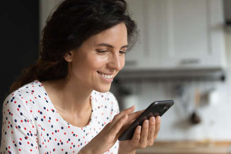 Happy Hispanic woman using apps and services on mobile phone at home, making quick payment, texting on social media chats, reading articles, shopping online on stores, watching videos on gadget