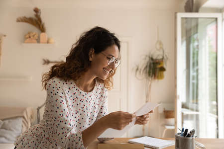 Happy Latin woman wearing glasses, reading paper letter at workplace at home, getting good news, receiving confirmation, application approval, certificate, event or party invitation, reviewing notice Фото со стока