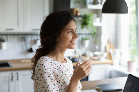 Happy female freelance employee working at laptop from home, taking break, drinking pure fresh water, looking away at window, thinking and smiling. Woman keeping healthy hydrate balance