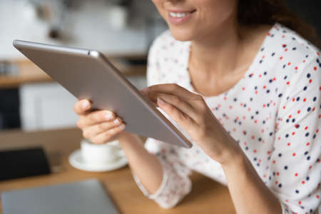 Happy female freelancer, shopper, customer, digital gadget user working from home, shopping online, using virtual app or service on tablet, making video call, reading book on internet. Close up