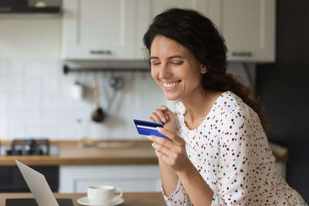 Happy female freelancer, entrepreneur using credit card with low servicing cost, good limit and cashback. Customer shopping online, paying for purchase, using bank payment service on laptop