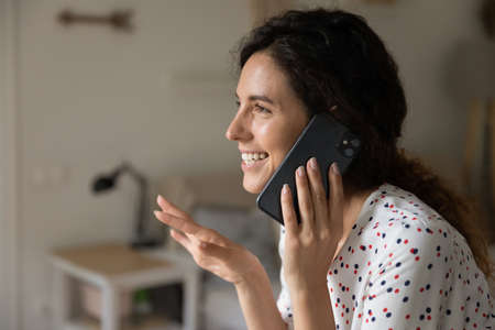 Excited laughing Latin woman speaking on cellphone, chatting to friend. Happy manager in casual working from home office, having phone call, giving consultation to client with friendly smile.