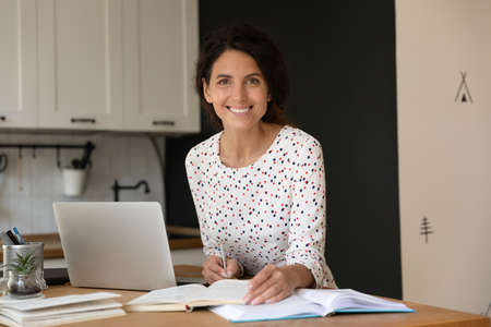 Happy female adult student with laptop and notebooks studying online from home, writing notes, preparing for exam, looking at camera, smiling. Distance learning, education concept. Head shot portrait