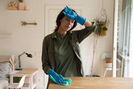 Tired overheated housewife doing domestic work at home, cleaning apartment. Exhausted woman wearing protective gloves, dusting furniture, suffering from heat, hot air. Household, overwork concept