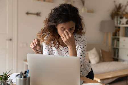 Woman tired of work at computer, taking off glasses, touching irritable eyes, eyelids, nose bridge. Remote employee, freelancer working from home, suffering from headache, vision, eyesight problems