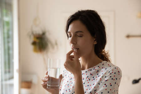 Stressed tired woman taking vitamins, painkillers, antidepressants, pills, meds against headache, insomnia, nervous disorder, anxiety. Patient with medication fighting against flu infection, migraine