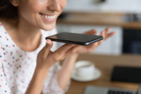 Happy freelance employee, distance manager, smartphone user giving voice command to virtual assistant, recording audio message, speaking at smartphone speaker during phone call talk. Close up