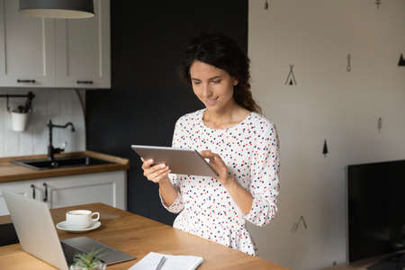 Happy female entrepreneur, employee, student with digital gadgets using online app on tablet for learning, accounting work, quick banking payment, shopping on internet, making video call